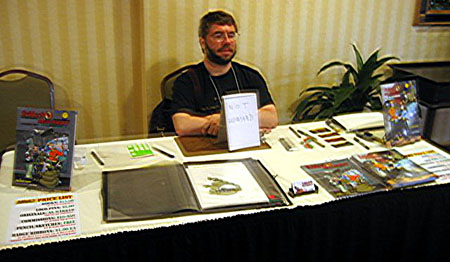 Paul Neubauer babysits Howard Tayler's Table at Penguicon 5.0
